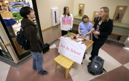 Iowa State University senior Scott Moseley spoke with ISU Atheist and Agnostic Society president Anastasia Bodnar at the Ask an Atheist booth at a campus community center.