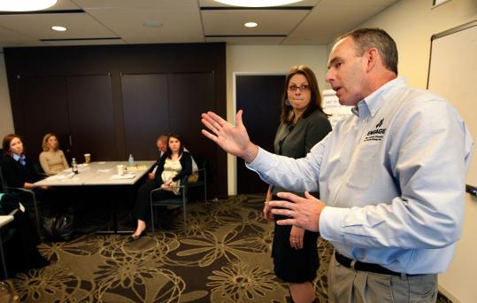 Bruce Campbell offered some pointers to Leslie Hirsh, an employee of Natixis Global Asset Management, during a class that included executives from Natixis and nonprofit groups. Campbell's firm, Engage, enlists corporate clients to share training with nonprofits.