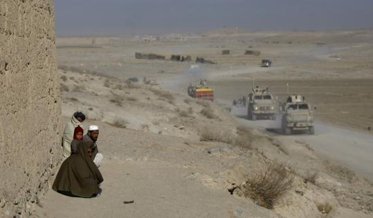 Afghans watched as armored vehicles from the Third Brigade Special Troops Battalion drive along a road near Pul-i-Alam.