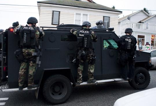 A Seattle police SWAT vehicle left a house after a fruitless search for the suspect in the slayings of officers Tina Griswold, Ronald Owens, Mark Renninger, and Greg Richards. Police believe the suspect was wounded in the coffee-shop attack early Sunday.