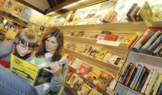 Lori Swain of Andover looks at a book with her son Jonathan, 10, at the Andover Bookstore, which is celebrating its 200th birthday.