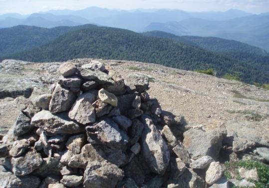 A cairn on the North Moat summit against a panorama of New Hampshire's White Mountains.