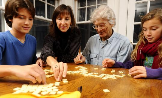 PHOTOS BY CHRISTINE HOCHKEPPEL FOR THE BOSTON GLOBE Members of the Nathanson family (from left) Aaron, Rena, Abe, and Ava play a game of Bananagrams at the very table where 80-year-old Abe invented it.