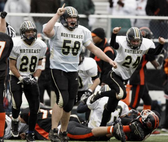 Northeast's Tyler Procopio (58), Oscar Desjardins (28) and John Huges (24) celebrate a crucial fumble recovery.