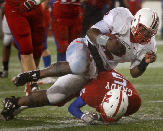 Reading quarterback Stanley Andre bowls over Natick's Pat Grady as he reaches the end zone in the fourth quarter.