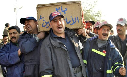 Members of Iraq's civil defense ministry carried the coffin yesterday of a colleague killed during this week's bombings. Prime Minister Nouri al-Maliki addressed Parliament in a bid to quell furor over the attacks.