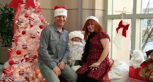 """Karson Tager (left) and Kennedy Elsey, hosts of Mix 104.1's """"Karson & Kennedy'' radio show, sat with Santa and helped out with donations yesterday at the Prudential Center mall."""
