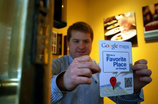 Chris Kane, an employee of Finale, attached a bar code to the front door of the Boston restaurant that customers will be able to scan, using a smartphone, to get information about the business.