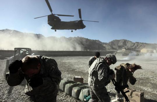 US army soldiers shielded themselves yesterday from swirling dust generated by a Chinook CH-47F transport helicopter in Paktya province in Afghanistan.