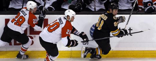 The Bruins' Marc Savard found himself a marked man when he led a rush up ice with Flyers in pursuit in the first period.