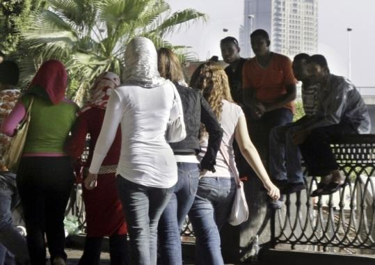 Boys watched girls walk past in Cairo last summer. Sexual harassment may be driving more women to cover up.