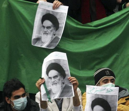 Iranian students on Sunday held pictures of the late revolutionary founder Ayatollah Khomeini, covering their faces to avoid being identified by security.