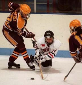 Kathryn Waldo helped lead the Northeastern Huskies to a conference title in 1997. The previous year, she split two Boston College players (above) at the Beanpot tournament, which NU won.