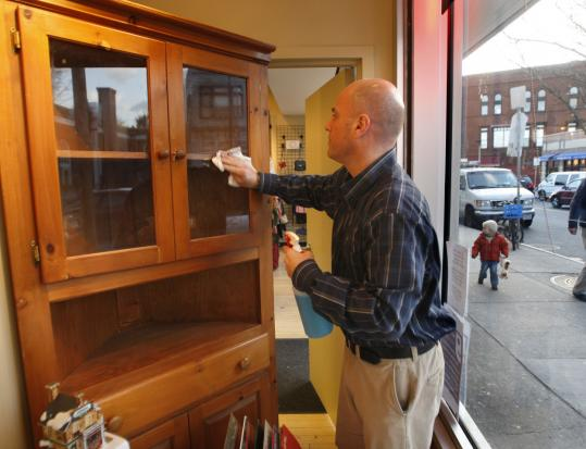 David Maglio, manager of the Goodwill store in Jamaica Plain, dusted a corner cabinet in the display window recently. The furniture was recently used during the filming of a major motion picture.