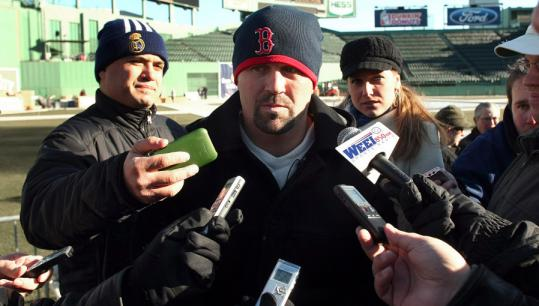 After circling the rink in Fenway, Jason Varitek is circled by the media.