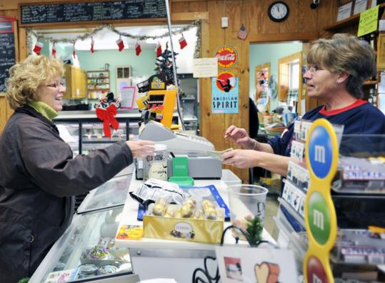 General store employee Lisa Marie Dupuis (right) rung up a purchase for customer Debbie Ellis, who Dupuis says comes to the store everyday.