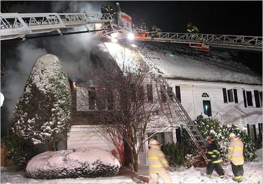 Firefighters battle a three-alarm blaze on Pickwick Road in Newton.
