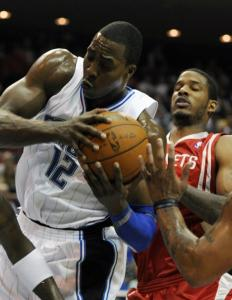 Orlando center Dwight Howard pulls down one of his 20 rebounds as he outmuscles Rockets' Trevor Ariza in the first half.