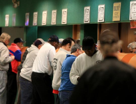 People lined up to place their bets during one of the afternoon dog races recently in Raynham.