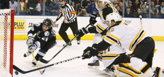With Vladimir Sobotka in the penalty box, Martin St. Louis of the Lightning pokes the puck in for a goal beyond the reach of Zdeno Chara and Dennis Wideman (right).