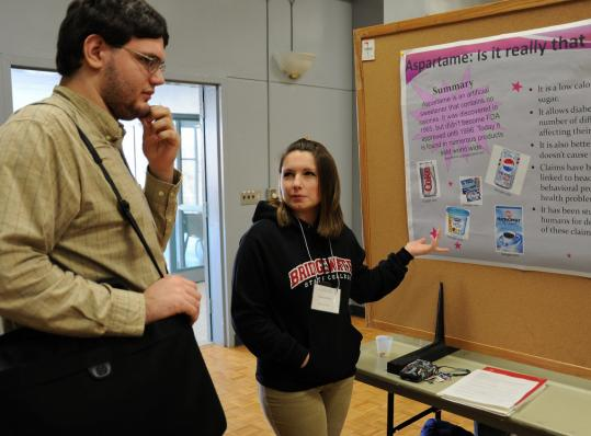 Elisa DeOlim (right) of Wareham presents her research during the Midyear Symposium at Bridgewater State College. The symposium exposes students to rigorous academic research.