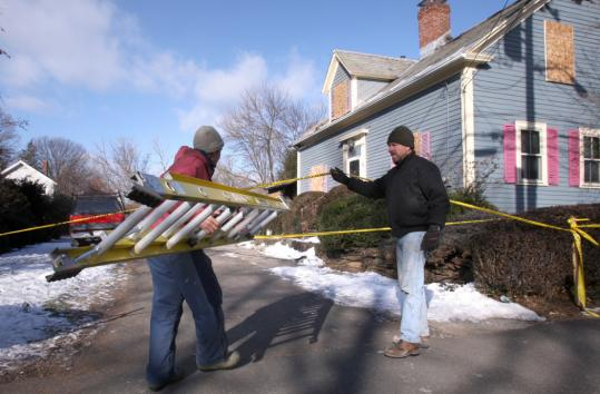 Kevin O'Brien (left) works on repairs for his sister's house, which was targeted in the attacks, with Mark Symanski.