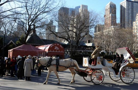 A Central Park horse-drawn carriage passed lunch customers Tuesday at Tavern on the Green, in operation since the mid-1970s. Interior decor will soon be auctioned to defray owners' debts.