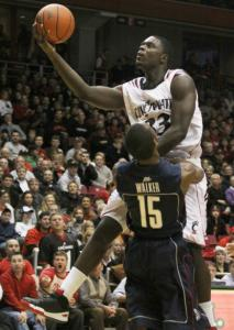 Bearcats' Lance Stephenson soars past UConn's Kemba Walker en route to 2 of his 21 points.