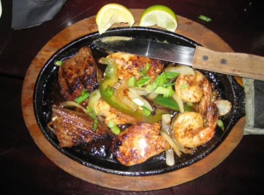 The Fox & Hound's Blackened Sampler is served in a cast-iron skillet and features shrimp, steak, and chicken topped with Cajun spices, citrus, peppers, and onions.