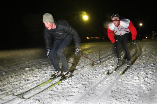 Cross-country skiers Hamish McEwen of Weston and Neil Garrison of Boxborough tackle the Weston Ski Track, which has expanded its lighting system.