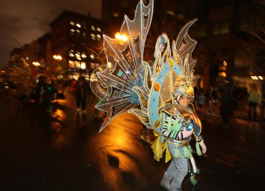 A tiny member of Dynasty Productions Inc. of Mattapan took part in the First Night parade in Boston, part of the 34th annual celebration of the arts and culture festival that has become a model for similar celebrations worldwide.
