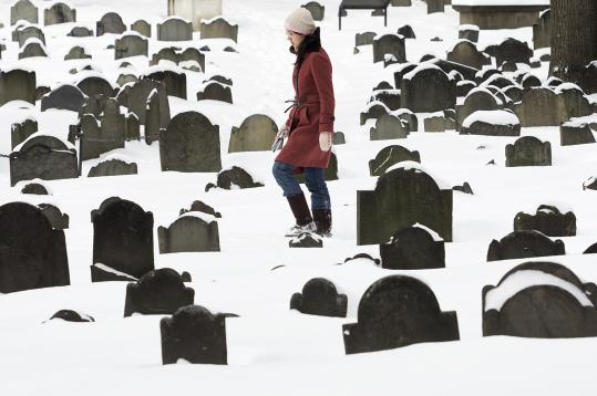 The fresh snow made a tour of the Granary Burying Ground a challenge yesterday for visiting Penn State student Rong Chen.