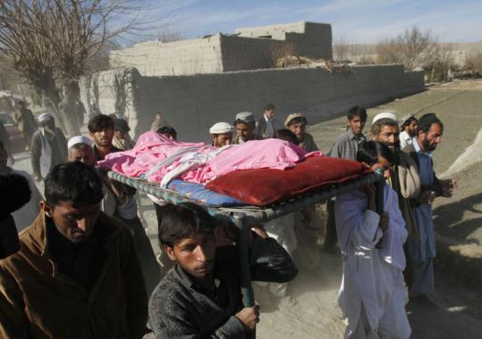 Relatives carried the body of a boy killed in a blast yesterday in Afghanistan. The government said the explosion occurred when a passing police vehicle hit a planted mine.