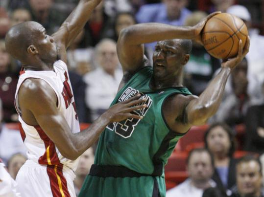 Kendrick Perkins, recovered from food poisoning, looks past the Heat's Joel Anthony in search of an open teammate.