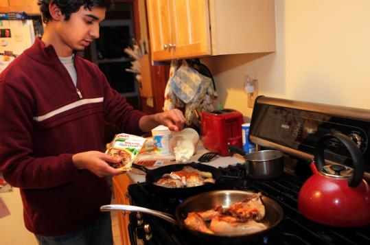 Mubashir Ghani Khawaja, 15, cooks dinner twice a week for his Maynard host family. Below: With Khawaja are Wendy Angus, Kelli Kirshtein, and their sons Daniel, 3, and Benjamin, 8.