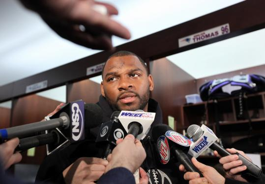 Adalius Thomas takes a break from cleaning out his locker at Gillette Stadium to talk to the media; he's one of several Patriots who may not return next season.