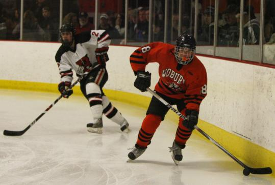 Woburn High's Dan Holland controls the puck in front of Reading's Kevin Gallagher last Saturday.