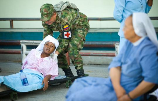 Sister Elida Vixamar received aid from a Colombian soldier yesterday in Port-au-Prince. The International Medical Surgical Response Team's cache of medical supplies was to arrive today.