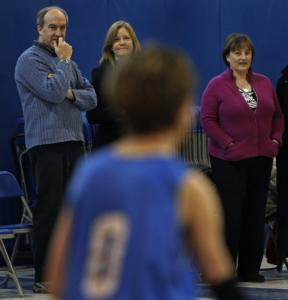 Head of school Steve Wilkens and trustees Lisa de Cristo and Morag Bamforth (from left) watch a basketball game at the Carroll School's new facility in Waltham last week.