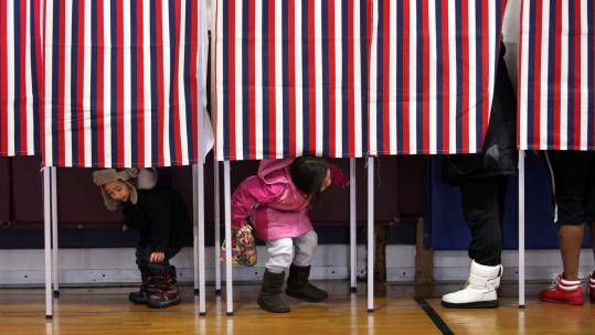 Maximus Vo (left), 2, and his sister, Trinity, 5, played while their mother, Trang Vo, cast her vote yesterday in Dedham.