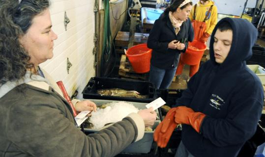Wendy Beagen hands in a voucher to pick up her share of shrimp from laborer Darrell Moore at the Yankee Fisherman's Cooperative in Seabrook.