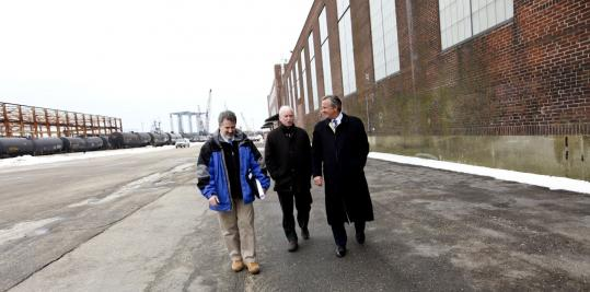 Project manager James Duffey, New England Aquarium president Bud Ris, and builder Jay Cashman (from left) tour the Fore River Shipyard building that will house the aquarium's new aquatic animal rehabilitation center. Below, Julie Cavin cares for a sea turtle at the aquarium's Boston headquarters.
