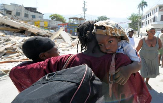 A Haitian man held his wife and child as they left their destroyed neighborhood in Port-au-Prince yesterday.