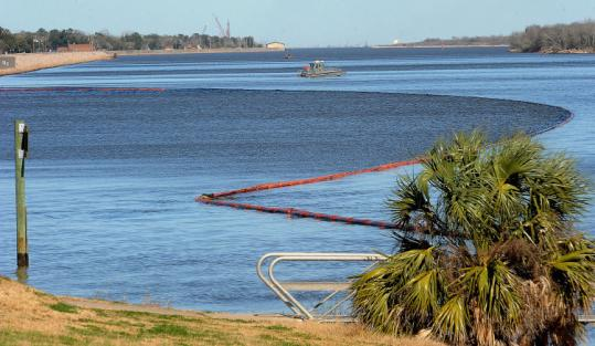 Booms stretched along the riverfront near Port Arthur as crews removed thousands of gallons of oil yesterday.