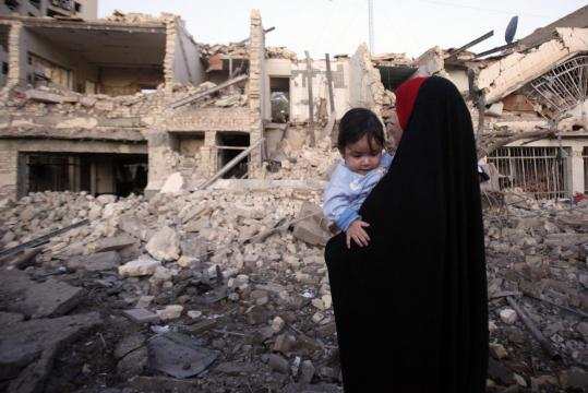 An Iraqi woman stood in front of her home after it was destroyed in a car bomb attack in Baghdad yesterday.