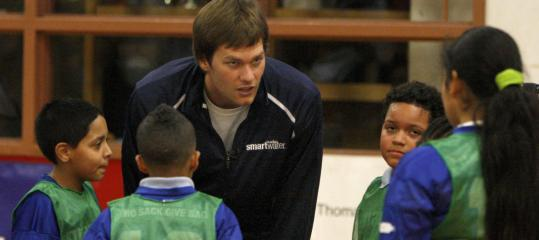 Tom Brady surveys the defense as he huddles up with kids at Roxbury&#8217;s Tobin Community Center.