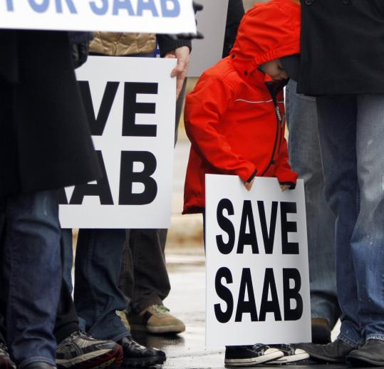 Jesper Hjertstedt, 4, held a sign at a Saab rally Sunday in Illinois. Below, a man took a picture of a Saab 96 grill on Jan. 17 in the Netherlands.