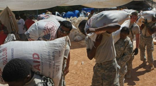 Soldiers from the 82d Airborne Division handled bags of food for the earthquake victims in Port-au-Prince yesterday.
