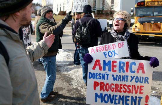 Demonstrators Timothy Larkin (left), who identified himself as a Socialist, and Linda Dupere, siding with the Tea Party Movement, expressed differing opinions yesterday near Nashua High School North, where President Obama spoke.