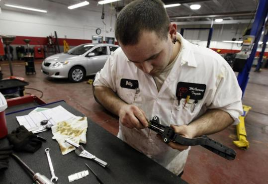 Line technician Bobby Rewoldt II, installs a shim into a CTS accelerator pedal for a 2010 Toyota Corolla at a Michigan dealership.